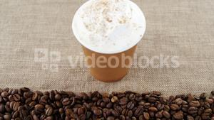 Disposable cup with coffee beans on sack