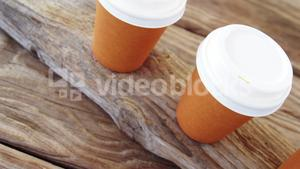 Disposable cup in a row on wooden plank
