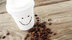 Smiley face on disposable cup with coffee beans on sack