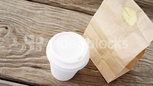 Disposable coffee cup and parcel on wooden plank