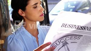 Businesswoman reading newspaper in café