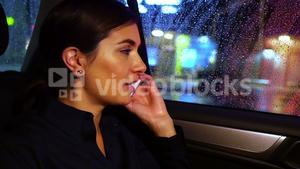 Businesswoman talking on mobile phone while travelling in car