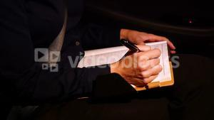 Businesswoman writing in diary while travelling in car