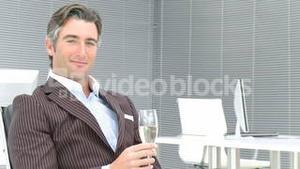 Business manager drinking champagne in office