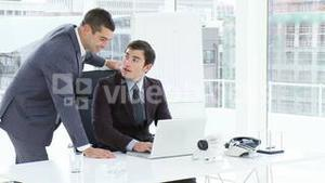 Businessmen talking and smiling in office