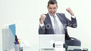 Happy businessman celebrating a success in business in office