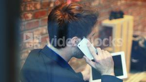 Man talking on mobile phone while using digital tablet