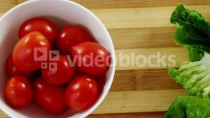 Lettuce and tomatoes in bowl on chopping board
