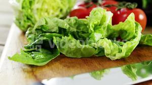 Vegetables and kitchen knife on wooden table