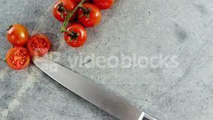 Cherry tomatoes and kitchen knife on concrete