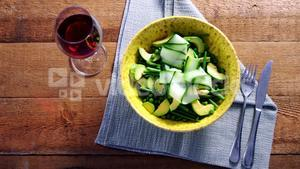 Salad with red wine on wooden table
