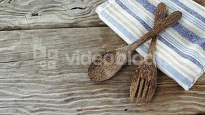 Wooden spoon and fork with napkin on table