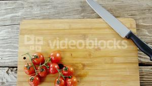 Cherry tomatoes and kitchen knife on chopping board