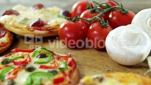 Italian pizza on wooden table with vegetables and spices
