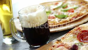 Delicious pizza with glasses of beer and soft drink