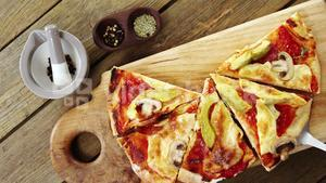 Delicious pizza with ingredients on wooden table
