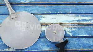 Pizza peel and cutter on wooden table