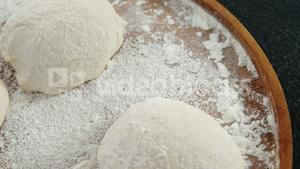 Pizza dough and flour on plate