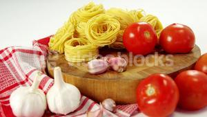 Tomatoes and raw pasta on chopping board
