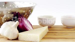 Cheese, onion and garlic with colander