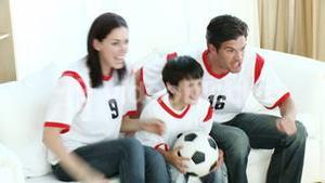 Family in Living Room watching Sport on TV