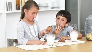 Brother and sister eating biscuits with milk