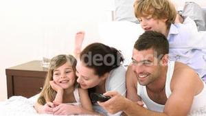 Family on a bed watching Television