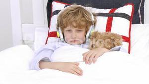 Young Boy on bed listening to Music