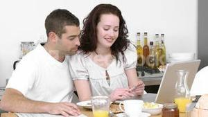 Couple working with a laptop in the kitchen