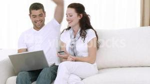 Young Couple at home using a laptop