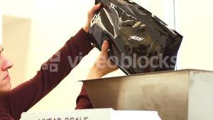 Mid-section of man packing coffee bag from sealing machine