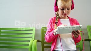 Girl listening to music from digital tablet