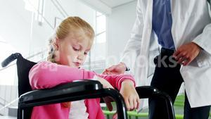 Disable girl sitting on wheel chair talking to doctor