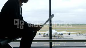 Businessman sitting at airport and reading newspaper