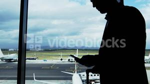 Businessman texting on mobile phone at airport