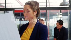 Beautiful business executive working over blueprint and smiling