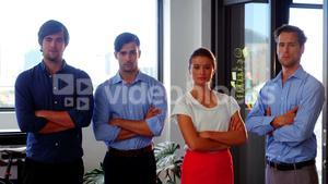 Confident business executives standing with arms crossed in office