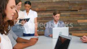 Business executives using laptop in office
