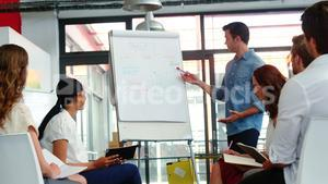 Man discussing design on white board with colleagues during a meeting