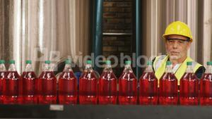 Worker checking juice bottles on production line