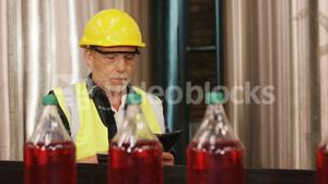 Worker using digital tablet in bottle factory