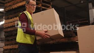 Worker arranging box in warehouse