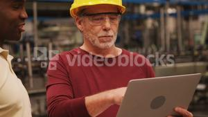 Workers discussing over laptop