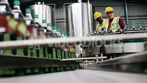 Workers checking bottles on production line