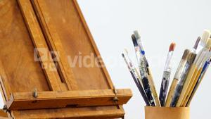 Easel and paintbrush on table