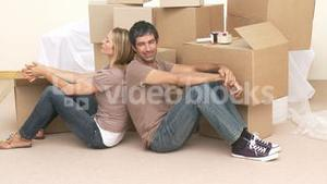 Tired couple sitting on floor after buying house