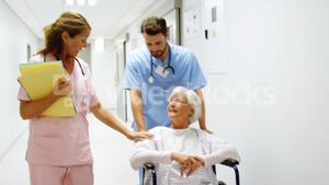 Nurse pushing a patient in a wheelchair while talking to a doctor