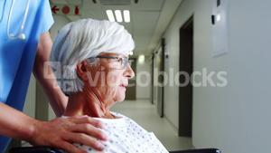 Nurse carrying female senior patient with wheel chair