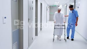 Male nurse assisting senior patient in using a walking frame