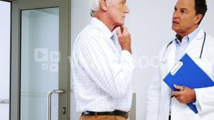 Male doctor interacting with male senior man in the passageway